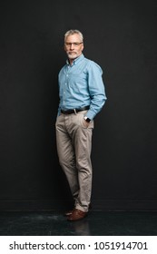 Full length photo of elderly businessman 70s with grey hair and beard posing on camera with smile and holding hands in pockets isolated over black background