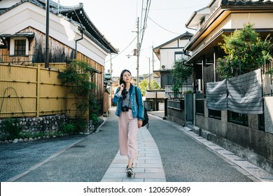 full length photo of an elegant lady walking in the path with Japanese traditional building around. Cheerful tourist travel in fun summer in Japan. Japanese lady going home.