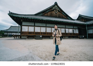 full length photo of an elegant tourist visiting the famous Japanese temple. travel photographer taking up slr camera to photographing. solo plan tourism in jp.