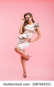 Full length photo of elegant trendy woman 20s in dress posing at camera with flirty look and touching fashionable sunglasses isolated over pink background