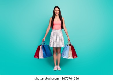 Full length photo energetic astonished girl shopping center client hold bags enjoy unbelievable discounts scream wow omg wear pink singlet checkered gumshoes isolated teal color background