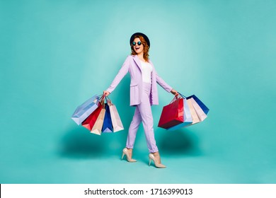 Full length photo of energetic woman worker go work tourist trip hold shopping bags wear violet blazer stilettos pants trousers formalwear cap isolated over teal turquoise color background