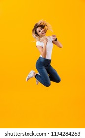Full length photo of european blond woman in basic clothing jumping and laughing isolated over yellow background