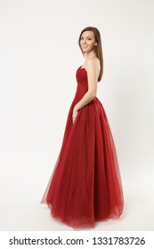 Full length photo fashion model woman wearing elegant evening dress red gown posing isolated on white wall background studio portrait. Brunette long hair girl. Mock up copy space. Side profile view