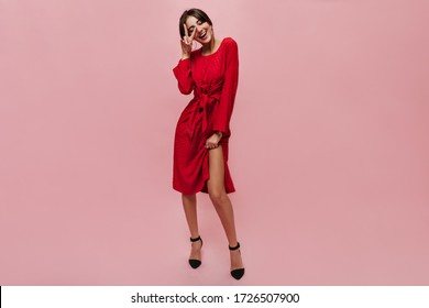 Full length photo of fashionable cool lady with round big earrings in midi red dress and black heels showing peace sign and smiling.