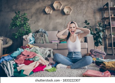 Full length photo frustrated shopaholic girl buy clothes prepare valentine day date have no idea what wear touch hands head scream sit floor carpet legs crossed in house indoors
