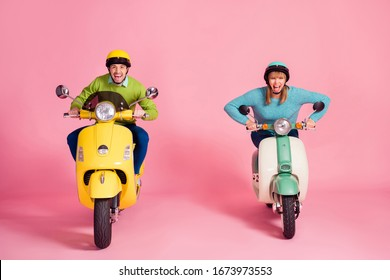 Full length photo of funny lady guy driving two vintage moped spend vacation together speed race competitive wear casual outfit colorful headgear isolated pink color background