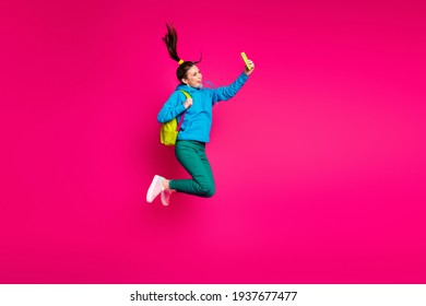 Full length photo of funny sweet young woman dressed blue hoodie rucksack taking selfie modern device isolated pink color background