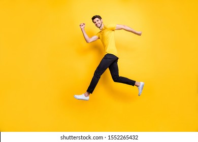 Full length photo of handsome guy jumping high speed running competition participant rushing shopping wear casual t-shirt black trousers isolated yellow color background