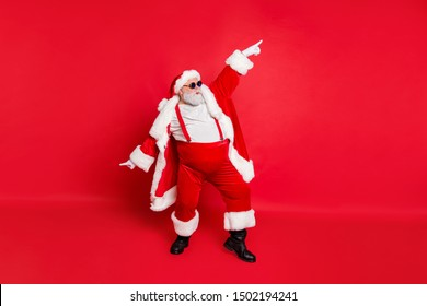 Full length photo of handsome old dabber fat funny santa claus in eyeglasses dance with his hand raised wearing style stylish trendy trousers pants isolated over red background