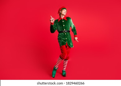 Full length photo of handsome x-mas north-pole jolly elf dance wear x-mas costume isolated red bright color background