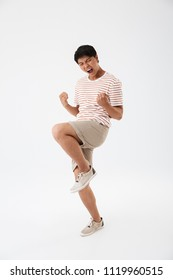 Full length photo of happy asian man 20s in casual striped t-shirt rejoicing with clenching fists isolated over white background