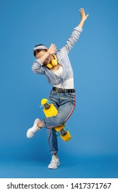 Full length photo of happy carefree young woman with yellow penny or skateboard and headphones dabbing over blue background.