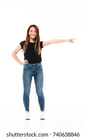 Full length photo of happy charming asian woman in casual wear standing with outstretched hand, pointing with finger, looking at camera, isolated on white background