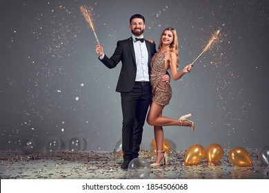 Full length photo of happy happy young loving couple standing isolated over grey background wall. Looking at camera with sparkle sticks cerebrate New Year.