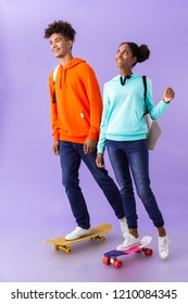 Full length photo of joyous african american people wearing backpacks smiling while skateboarding isolated over violet background