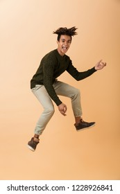 Full length photo of joyous african american guy wearing sweater laughing and jumping isolated over beige background