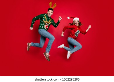Full length photo of jumping couple excited by x-mas prices hurry buy costumes wear ugly ornament jumpers isolated red color background