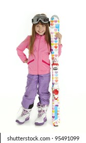 Full length photo of little girl dressed in ski wear holding colorful skis, standing on white background.