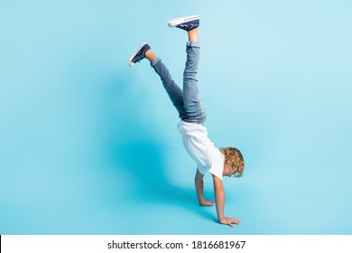 Full length photo of little kid stand hands raise legs wear white shirt jeans sneakers isolated blue color background
