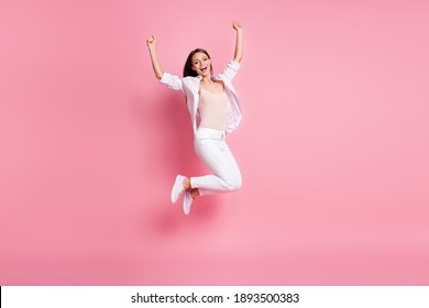 Full length photo of lucky surprised young woman dressed casual white clothes rising two fists isolated pastel pink color background