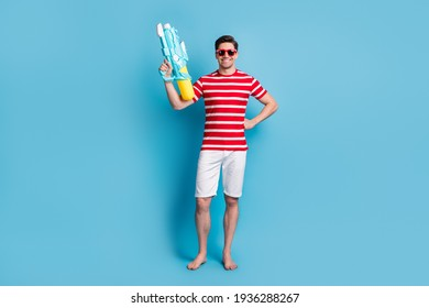 Full length photo of positive cool man hold water gun play game summer time isolated on blue color background