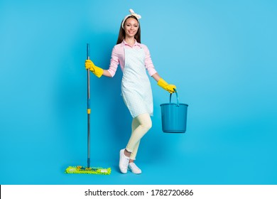 Full length photo of positive maid girl hold bucket mop ready wash floor protect home coronavirus infection epidemic wear trendy pink shirt pants trousers isolated blue color background