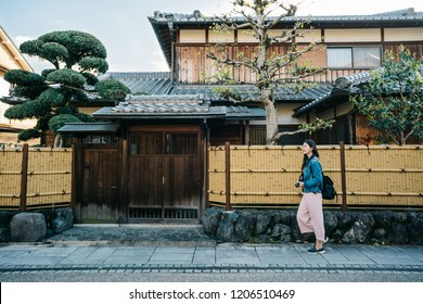 full length photo of a pretty lady walking by the Japanese traditional building house. self-guided trip in Kyoto jp. Travel Japan summer holiday girl enjoying city.
