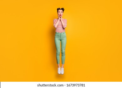 Full length photo of pretty lady jumping high up traveler abroad see big prices shopping missed sales wear red white shirt green pants footwear isolated bright yellow background