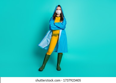 Full length photo of pretty lady rainy weather use medical infection flu mask quarantine distancing arms crossed wear raincoat sweater pants gumboots isolated teal color background