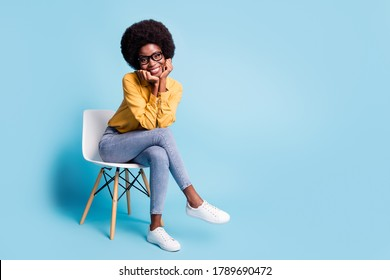 Full length photo of pretty lovely dark skin girl sit chair touch hands chin wear good look casual outfit isolated over blue pastel color background