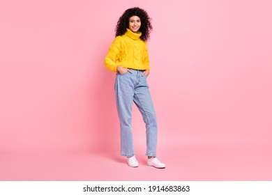 Full length photo of pretty shiny curly woman wear yellow pullover standing arms pockets isolated pink color background