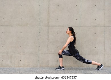 full length photo of pretty sporty young woman warm up stretching legs before morning running workout outdoor on gray wall background city building walkway.