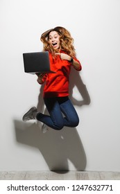 Full length photo of pretty woman 20s wearing red sweatshirt jumping and holding gray laptop isolated over white background