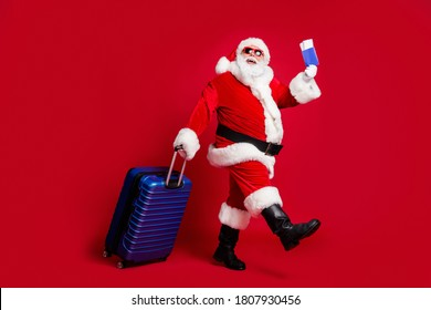 Full length photo of retired old man white beard hold suitcase tickets passport check-in airport wear x-mas santa costume glove coat belt sunglass cap boot isolated red color background