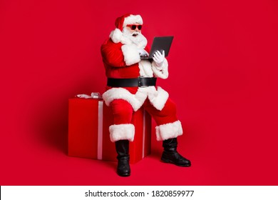 Full length photo of retired old man white beard sit giftbox hold laptop take orders online wear x-mas santa costume glove coat belt sunglass cap boot isolated red color background - Shutterstock ID 1820859977