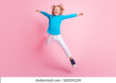 Full length photo of small boy jump star pose wear blue turtleneck pants sneakers isolated pastel pink color background