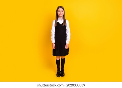 Full length photo of small cute girl stand wear black uniform isolated on yellow color background