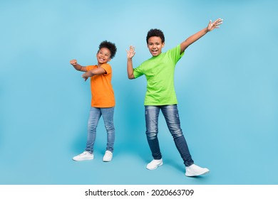 Full length photo of small funny brunet boy girl dance wear t-shirt jeans shoes isolated on blue color background - Shutterstock ID 2020663709