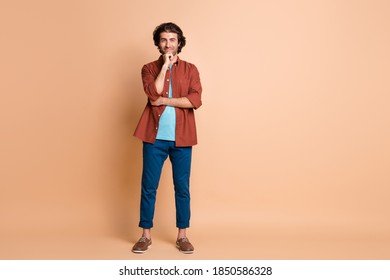 Full length photo of smart guy look camera hand chin wear brown t-shirt blue pants footwear isolated beige color background