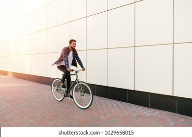 Full length photo of smiling young bearded man riding a bike on the city street. Dressed up in plaid shirt, t-shirt and jeans. Recreation concept.
