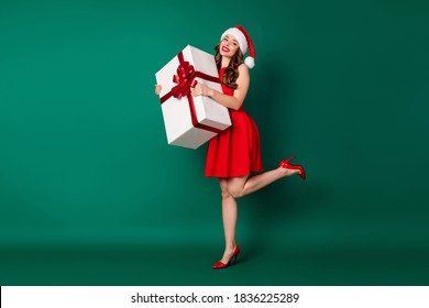 Full length photo stunning pretty cute sweet girl in santa claus headwear hold big gift box prepare x-mas jolly holly newyear event wear legs skirt high-heels isolated green color background