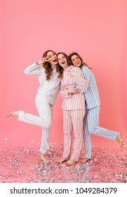 Full length photo of three beautiful teenage women 20s wearing leisure clothings hugging and having fun at slumber party isolated over pink background