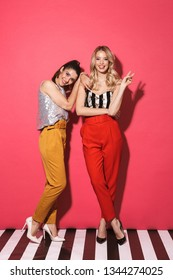 Full length photo of two caucasian women 20s in trendy outfit smiling at camera and standing isolated over red background