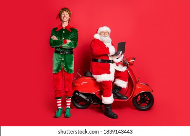 Full length photo of two men elf folded arms santa sit moped hold netbook wear x-mas costume coat cap boots isolated red color background