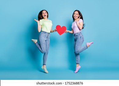 Full length photo of two people pretty lesbians couple ladies jump high up hold big red paper heart lovers valentine day celebration wear casual t-shirts jeans isolated blue color background