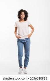 Full length photo of vivacious american woman wearing jeans and t-shirt posing on camera with candid smile and hands in pocket isolated over white background