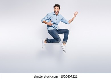 Full length photo of wild multiethnic guy jumping high at hard rock concert playing imagine electric guitar wear casual denim clothes isolated white color background