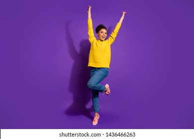 Full length photo of wild youth raise hands arms scream shout wear jeans yellow pullover isolated over purple violet background