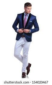 full length photo of a young business man unbuttoning the jacket of his suit while looking away from the camera. on a white background